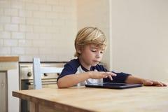 Молодой мальчик используя планшет на кухонном столе Стоковые Фотографии RF