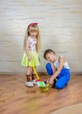 Молодой мальчик и девушка помогая убрать дом Стоковое Изображение RF