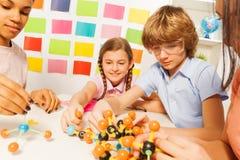 Молодой мальчик и девушки собирая модель молекулы Стоковые Фото