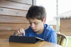 Молодой мальчик и таблетка цифровая Стоковые Изображения