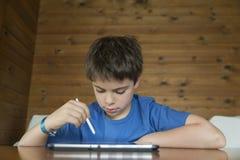 Молодой мальчик и таблетка цифровая стоковая фотография rf