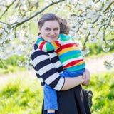 Молодой мальчик мамы и маленького ребенка в зацветая саде Стоковые Фотографии RF