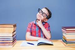 Молодой мальчик мечтает на столе в школьной библиотеке Стоковые Изображения RF