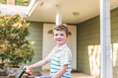 Молодой мальчик на велосипеде дома Стоковые Фото