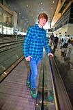 Молодой мальчик на moving лестнице внутри авиапорта Стоковые Изображения RF