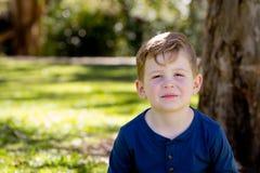 Молодой мальчик нежно усмехаясь и сидя пересеченное шагающее против дерева Стоковое фото RF