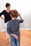 Молодой мальчик обжуливает - будьте матерью смотреть сердитый Стоковые Изображения RF