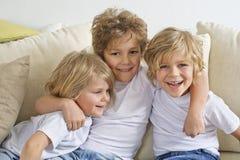 Молодой мальчик обнимая его 2 братьев Стоковое Изображение