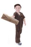 Молодой мальчик поставляя пакет к телезрителю стоковые фото