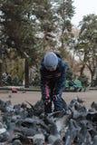 Молодой мальчик подавая птицы в Алма-Ате в Казахстане Стоковые Фотографии RF