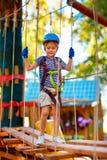 Молодой мальчик проходя максимум среди деревьев, весьма спорт трассы кабеля в парке приключения Стоковое фото RF