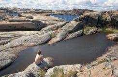 Молодой мальчик сидя на утесе и смотря на море Стоковые Изображения RF
