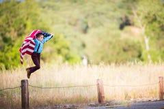 Молодой мальчик скача с американским флагом Стоковые Фото