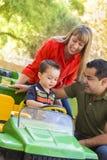 Молодой мальчик смешанной гонки наслаждается трактором игрушки с родителями стоковое изображение rf