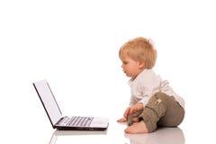 Молодой мальчик смотря компьтер-книжку Стоковые Фото