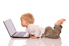 Молодой мальчик смотря компьтер-книжку Стоковое Фото