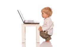 Молодой мальчик смотря компьтер-книжку Стоковые Изображения