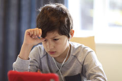 Молодой мальчик смотря таблетку Стоковые Фотографии RF