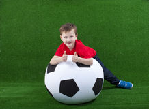 Молодой мальчик с огромным футбольным мячом стоковое фото