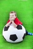 Молодой мальчик с огромным футбольным мячом Стоковая Фотография