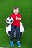 Молодой мальчик с огромным футбольным мячом стоковые изображения rf