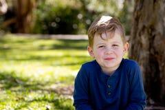 Молодой мальчик тихо сидя пересеченное шагающее против ствола дерева в p Стоковые Фотографии RF