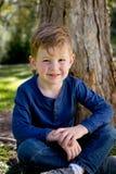 Молодой мальчик усмехаясь и сидя пересеченное шагающее против ствола дерева Стоковое Изображение