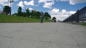 Молодой мальчик уча ехать скейтборд в сток-видео