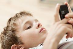 Молодой мальчик читая текстовое сообщение на его черни Стоковая Фотография