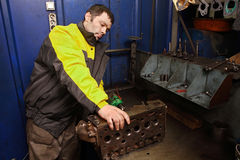 Молодой механик автомобиля очищает каналы двигателя головки цилиндра Стоковые Фото