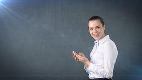 Молодой милый конец коммерсантки вверх по портрету держа мобильный телефон в ее руках и наблюдая его Изолированная предпосылка ст Стоковая Фотография