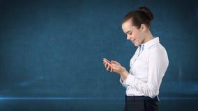 Молодой милый конец коммерсантки вверх по портрету держа мобильный телефон в ее руках и наблюдая его Изолированная предпосылка ст Стоковое Изображение