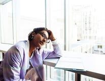 Молодой милый студент девушки битника сидя в кафе с чтением тетради, нося стеклами, людьми образа жизни счастливыми усмехаясь Стоковая Фотография RF
