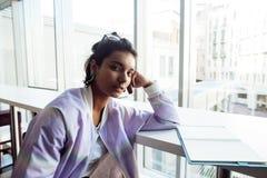 Молодой милый студент девушки битника сидя в кафе с чтением тетради, нося стеклами, людьми образа жизни счастливыми усмехаясь Стоковая Фотография