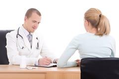 Молодой мужские доктор и женщина говоря в офисе изолированном на белизне Стоковые Изображения RF