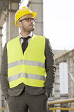 Молодой мужской архитектор в руках защитного workwear стоящих в карманн на строительной площадке Стоковая Фотография RF