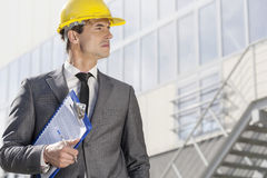 Молодой мужской архитектор при доска сзажимом для бумаги смотря отсутствующее внешнее офисное здание Стоковые Изображения RF