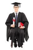 Молодой мужской аспирант сидя на стуле и держа диплом Стоковое Изображение