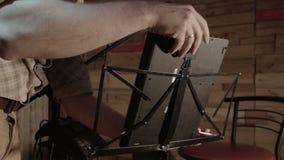 Молодой мужской музыкант инженера устанавливает на шкаф компьтер-книжки видеоматериал