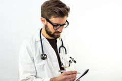 Молодой мужской доктор принимая примечания Стоковые Фотографии RF
