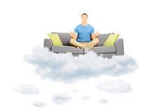 Молодой мужской размышлять на софе и плавать на облако стоковая фотография