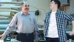 Молодой мужской тренирующая и старший владелец бизнеса говоря и усмехаясь в мастерской Стоковое Изображение