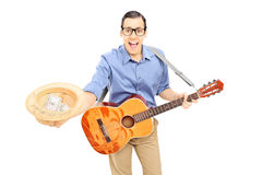 Молодой мужской уличный исполнитель с гитарой собирая деньги в его Стоковое Изображение RF
