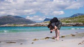 Молодой мужской фотограф с dreadlocks на солнечном пляже с белым песком, Стоковое фото RF