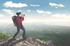 Молодой мужчина принимая фото на горе Стоковая Фотография