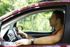 Молодой мужчина управляя автомобилем стоковые фото