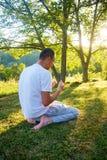 Молодой мусульманский человек молит в природе на времени захода солнца Стоковые Изображения RF