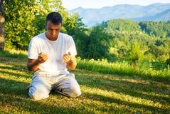 Молодой мусульманский человек молит в природе на времени захода солнца Стоковая Фотография RF