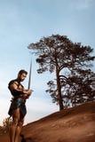 Молодой мышечный ратник с шпагой на горах стоковое изображение rf