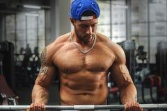 Молодой мышечный человек делая тренировку с штангой Стоковое Изображение RF